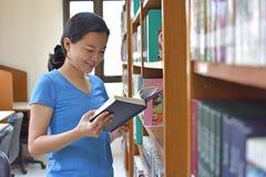 读一本书的愉快的妇女在图书馆里 免版税库存照片