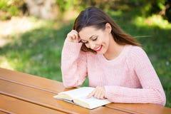 读一本书的美丽的少妇在公园 免版税库存图片