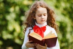 读一本书的聪明的小女孩在公园 库存照片