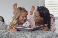 读一本故事书的母亲和女儿在卧室 免版税库存照片