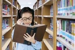 读一本课本的小女孩在图书馆里 库存照片