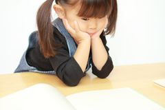 读与她的下巴的日本女孩一本画书在她的手上 免版税库存照片