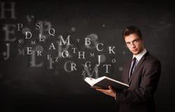 读与字母表信件的年轻人一本书 图库摄影
