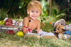 读与玩具的女孩一本书在庭院里 图库摄影