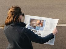 读世界报法语的妇女按安格拉・默克尔竞选毒菌 图库摄影