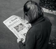 读世界报法语的妇女按安格拉・默克尔竞选毒菌 库存图片