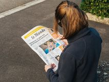 读世界报法语的妇女按安格拉・默克尔竞选毒菌 免版税图库摄影