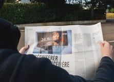 读世界报法语的妇女按安格拉・默克尔竞选毒菌 免版税库存图片