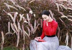 读书和听到音乐的女孩 有书的白肤金发的美丽的少妇坐草 室外 晴朗的日 库存图片