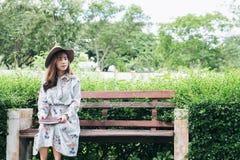 读书和放松在公园的可爱的亚裔妇女 库存照片