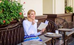 读书是她的爱好 抢劫咖啡和有趣的书最佳的组合完善的周末 女孩饮料咖啡,当读时 免版税库存照片
