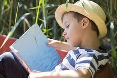 读书的一个小甜男孩的画象 免版税图库摄影