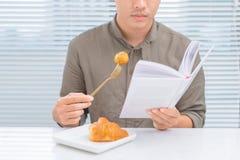 读书的亚裔人在吃早餐期间早晨 免版税库存照片