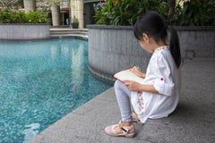 读书的亚裔矮小的中国女孩 库存图片