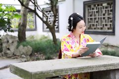 读书的传统亚裔日本妇女坐一条石长凳在庭院里 库存图片