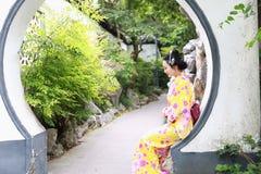 读书的传统亚裔日本妇女坐一条石长凳在庭院里 免版税库存图片