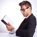 读书的商人的侧视图 免版税库存照片