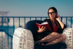 读书的夏天妇女由海滩在度假 免版税库存照片