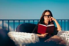 读书的夏天妇女由海滩在度假 免版税图库摄影