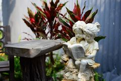 读书的女孩和男孩雕象在庭院里 库存图片