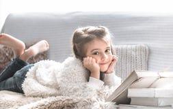 读书的女孩在一个舒适的沙发,美好的情感 免版税库存照片