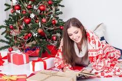 读书的女孩在圣诞树圣诞节礼物附近 库存图片