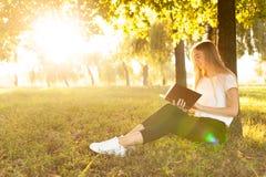 读书的女孩坐在公园在树附近在日落 免版税库存图片