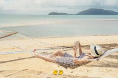 读书的妇女在吊床海滩在时间夏天休假 库存照片