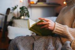 读书的妇女,坐在与kn的一把舒适椅子它在壁炉前面的格子花呢披肩,冬天舒适概念,软的被定调子的图象 库存图片