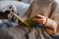 读书的妇女,坐在与kn的一把舒适椅子它在壁炉前面的格子花呢披肩,冬天舒适概念,软的被定调子的图象 免版税库存图片