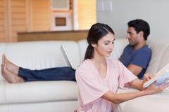 读书的妇女,当她的未婚夫使用一台膝上型计算机时 图库摄影