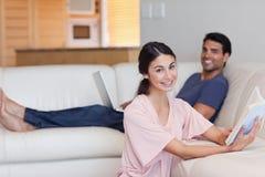 读书的妇女,当她的男朋友使用一台膝上型计算机时 库存图片