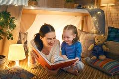 读书的妈妈和孩子 免版税图库摄影