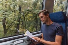 读书的年轻帅哥,当旅行乘火车时 免版税库存图片