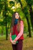 读书的年轻浪漫女孩坐草 库存图片