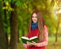 读书的年轻浪漫女孩坐草 免版税库存照片