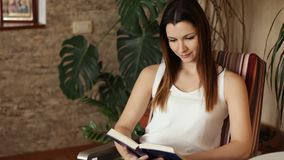 读书的年轻美丽的女孩坐在椅子 微笑可爱的妇女,当读书时 正的情感 股票视频