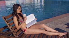 读书的年轻美丽的妇女在游泳池附近 股票视频