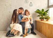 读书的愉快的家庭对她的女儿 日花产生母亲妈咪儿子 免版税库存照片