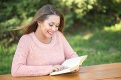 读书的美丽的女孩外面 免版税库存图片