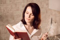 读书的美丽的年轻红头发人妇女,当烹调在厨房时 免版税库存照片