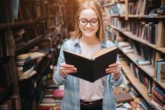 读书的聪明的学生的明亮和温暖的图片 女孩微笑着并且继续进一步读书 免版税图库摄影
