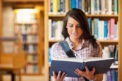 读书的逗人喜爱的新学员 免版税库存照片