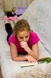 读书的青少年的女孩在床 图库摄影