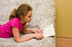 读书的青少年的女孩在床 库存图片