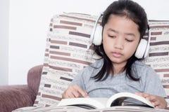 读书的Childern在沙发 免版税库存图片