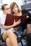读二的美丽的女孩纸张 免版税库存照片
