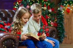 读兴趣的孩子预定坐床反对 免版税库存照片