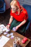 读占卜卡片的成熟白肤金发的妇女戴着眼镜顶视图  免版税库存图片