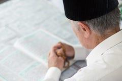 读古兰经的一个老人 免版税库存图片